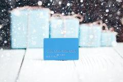 Tarjeta de crédito azul de la composición del Año Nuevo de la Navidad con los regalos en vagos Fotografía de archivo libre de regalías