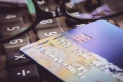 Tarjeta de crédito con los vidrios en una calculadora Imágenes de archivo libres de regalías
