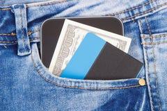 Tarjeta de crédito, dólar de las monedas y smartphone en bolsillo de los vaqueros Concepto del pago al contado Cashless o fotos de archivo