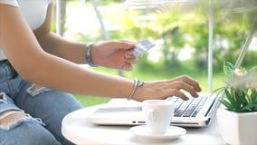 Tarjeta de crédito el mecanografiar joven y de la transacción de la señora en el ordenador portátil Imagen de archivo libre de regalías