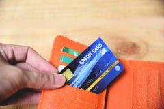 Tarjeta de cr?dito en cartera con la mano - en l?nea pagando del concepto casero o creciente de la tarjeta de cr?dito de la deuda imagen de archivo libre de regalías