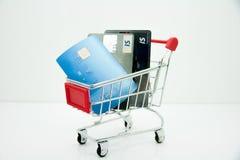 Tarjeta de crédito en el carro de la compra aislado en el fondo blanco fotos de archivo