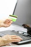 Tarjeta de crédito en manos maduras Imagenes de archivo