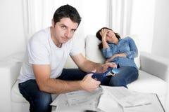 Tarjeta de crédito joven del corte del marido con la mujer de las tijeras presionada Imagen de archivo