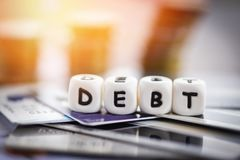 Tarjeta de cr?dito de la deuda y pila de la moneda del dinero/responsabilidades crecientes del concepto de la consolidaci?n de de imagen de archivo