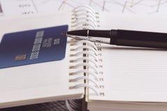 Tarjeta de crédito y pluma de bola en un organizador Foto de archivo