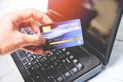 Tarjeta de cr?dito y usar el concepto que hace compras en l?nea del pago f?cil del ordenador port?til - tarjeta electr?nica a dis foto de archivo libre de regalías