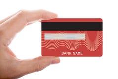 Tarjeta de cr?dito roja de la tenencia de la mano aislada en el fondo blanco foto de archivo libre de regalías