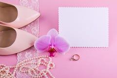 Tarjeta de felicitación blanca con el borde ondulado Zapatos de cuero beige con el tacón alto, la tarjeta de felicitación y los a Fotos de archivo libres de regalías