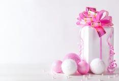 Tarjeta de felicitación blanca con el espacio de la copia para la Navidad o el Año Nuevo con un regalo envuelto y una bola rosada Fotos de archivo