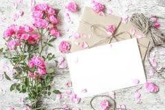 Tarjeta de felicitación blanca en blanco con el ramo rosado de las rosas Imágenes de archivo libres de regalías