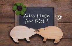 Tarjeta de felicitación con el trébol y dos cerdos de madera - como un par - Imagen de archivo