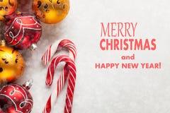 Tarjeta de felicitación con la Navidad y el Año Nuevo La Feliz Navidad de la inscripción y la Feliz Año Nuevo en un hormigón blan Imagen de archivo