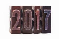 Tarjeta 2017 de felicitación de la Feliz Año Nuevo escrita con el tipo coloreado de la prensa de copiar del vintage Fondo blanco  Imágenes de archivo libres de regalías