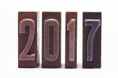 Tarjeta 2017 de felicitación de la Feliz Año Nuevo escrita con el tipo coloreado de la prensa de copiar del vintage Fondo blanco  Imagen de archivo libre de regalías