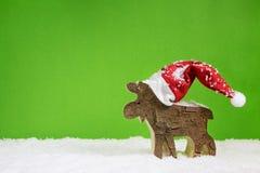 Tarjeta de felicitación de la Navidad con el reno en cuesta roja y blanca verde Foto de archivo libre de regalías
