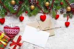 Tarjeta de felicitación de la Navidad con el sobre en el fondo de madera blanco Imágenes de archivo libres de regalías