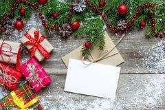 Tarjeta de felicitación de la Navidad con las cajas de regalo, el árbol de abeto y la decoración Imágenes de archivo libres de regalías