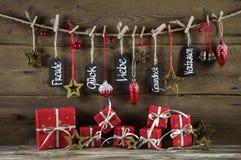 Tarjeta de felicitación de la Navidad con los presentes del rojo y los buenos deseos en Ger Fotos de archivo