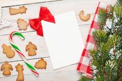 Tarjeta de felicitación de la Navidad, galletas del pan de jengibre y árbol de abeto de la nieve Imágenes de archivo libres de regalías