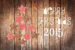 Tarjeta de felicitación de la Navidad 2015, ornamentos rústicos en el fondo de madera de los tablones Fotos de archivo libres de regalías