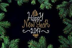 Tarjeta de felicitación de la Navidad y del Año Nuevo con el marco de los brunches del árbol y el Dr. spruce de la mano Foto de archivo libre de regalías
