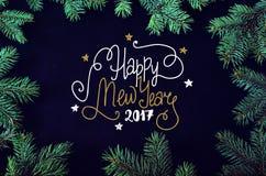 Tarjeta de felicitación de la Navidad y del Año Nuevo con el marco spruce de los brunches del árbol Foto de archivo