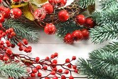 Tarjeta de felicitación de la Navidad y del Año Nuevo con las bayas y la conífera Imagen de archivo libre de regalías