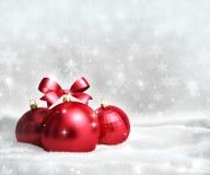 Tarjeta de felicitación de la Navidad y del Año Nuevo con las bolas rojas en nieve y espacio para el texto Imagen de archivo