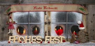 Tarjeta de felicitación de madera de Navidad con el texto alemán y las velas rojas: Merr Fotografía de archivo