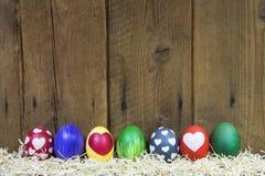 Tarjeta de felicitación de Pascua con diversos huevos coloridos en la madera. Foto de archivo libre de regalías