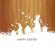 Tarjeta de felicitación de Pascua con el conejo, el regalo y las luces en el fondo de madera