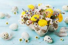 Tarjeta de felicitación de Pascua con las flores, la pluma y los huevos de codornices coloridos en la tabla de la turquesa del vi imagen de archivo