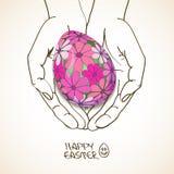Tarjeta de felicitación de Pascua con las manos humanas que sostienen el huevo Foto de archivo libre de regalías