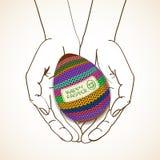 Tarjeta de felicitación de Pascua con las manos humanas que sostienen el huevo hecho punto Foto de archivo