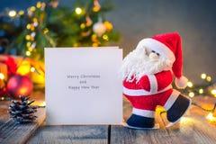 Tarjeta de felicitación decorativa de Santa Claus que lleva con recuerdos en el fondo oscuro festivo con el árbol de navidad, las Foto de archivo