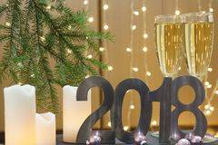 Tarjeta de felicitación del Año Nuevo 2018 con la rama de árbol, las velas blancas y las bolas rosadas de la Navidad Foto de archivo libre de regalías