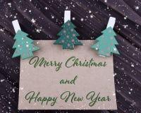 Tarjeta de felicitación del Año Nuevo de Navidad de la Navidad con el árbol de navidad en pinzas en fondo de madera oscuro Imagen de archivo libre de regalías