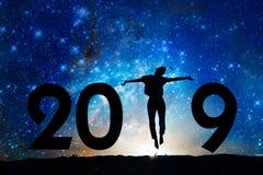 Tarjeta de felicitación del Año Nuevo 2019 Silueta de una mujer que salta en la noche imagenes de archivo
