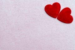Tarjeta de felicitación del día de tarjetas del día de San Valentín con dos corazones rojos sobre fondo rosado del brillo con el  Fotos de archivo