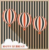 Tarjeta de felicitación del feliz cumpleaños con los globos del aire caliente, el fondo hecho de rayas y la nube blanca Imágenes de archivo libres de regalías