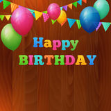 Tarjeta de felicitación del feliz cumpleaños con los globos en el fondo de madera Foto de archivo libre de regalías