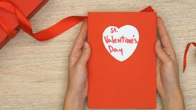 Tarjeta de felicitación del St día de San Valentín de la tenencia de la señora, giftbox en la tabla, presente romántico metrajes