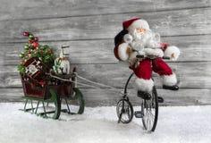 Tarjeta de felicitación divertida de la Navidad con Papá Noel en una bici que tira de un sli imagen de archivo