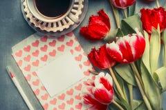 Tarjeta de felicitación en blanco con los corazones y lápiz, tulipanes bonitos y taza de café, visión superior Imágenes de archivo libres de regalías
