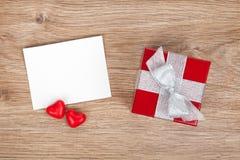 Tarjeta de felicitación en blanco de las tarjetas del día de San Valentín y pequeña caja de regalo roja imágenes de archivo libres de regalías