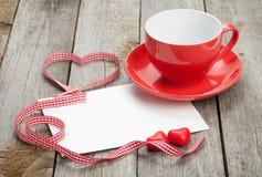 Tarjeta de felicitación en blanco de las tarjetas del día de San Valentín y taza de café roja Fotografía de archivo libre de regalías