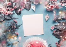 Tarjeta de felicitación en blanco en el escritorio azul del florista con las flores rosadas, los corazones y la fan de papel de l imagenes de archivo
