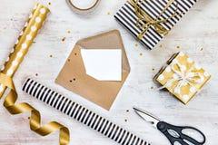 Tarjeta de felicitación en blanco en un sobre del arte, cajas de regalo y materiales de embalaje en un fondo de madera blanco Imagen de archivo