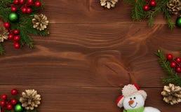 Tarjeta de felicitación en fondo de madera con las decoraciones de la Navidad Imagen de archivo libre de regalías
